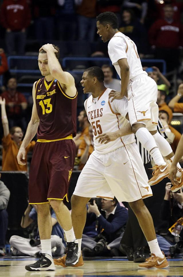 Texas center Cameron Ridley (55) celebrates his game winning shot with Texas guard Isaiah Taylor as Arizona State center Jordan Bachynski (13) walks off after a second-round game in the NCAA college basketball tournament Thursday, March 20, 2014, in Milwaukee. Texas won 87-85. (AP Photo/Jeffrey Phelps)