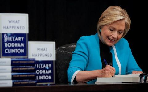 Hillary Clinton signs a copy of her new book in New York  - Credit: ANDREW KELLY/ REUTERS