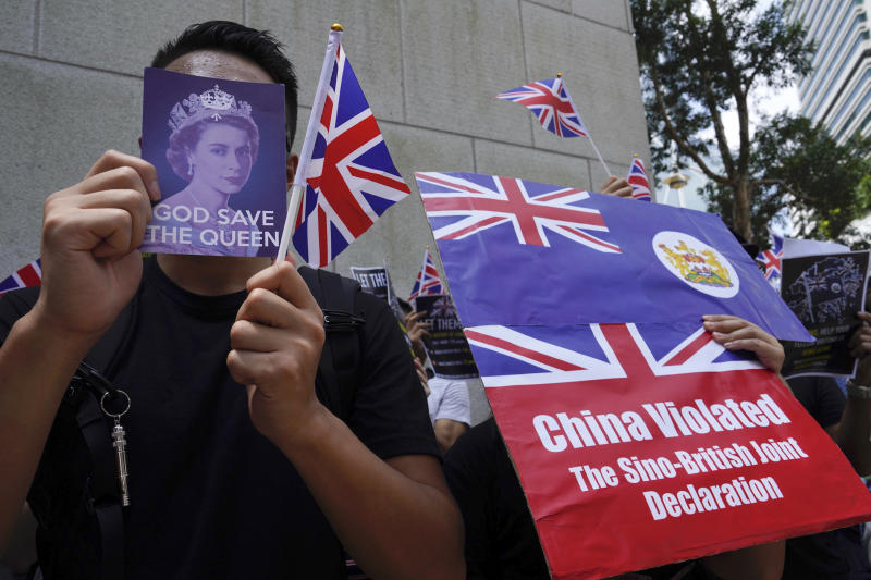 Protesters hold British flags and placards during a peaceful demonstration outside the British Consulate in Hong Kong, Sunday, Sept. 15, 2019. Hundreds of Hong Kong activists rallied outside the Consulate for a second time this month, bolstering calls for international support in their months-long protests for democratic reforms in the semi-autonomous Chinese territory. (AP Photo/Vincent Yu)