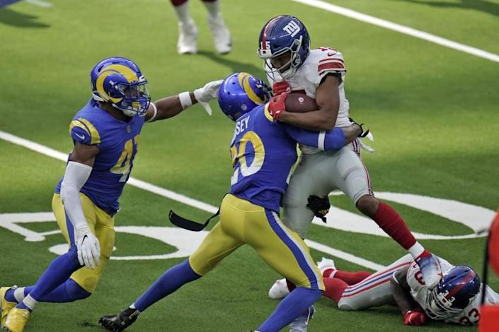 New York Giants wide receiver Golden Tate, right, is tackled by Los Angeles Rams cornerback Jalen Ramsey.