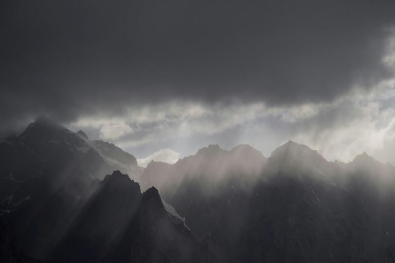 The sun's rays shine through clouds over the Karakorum mountain range next to the China-Pakistan Friendship Highway near Tashkurgan in western Xinjiang province