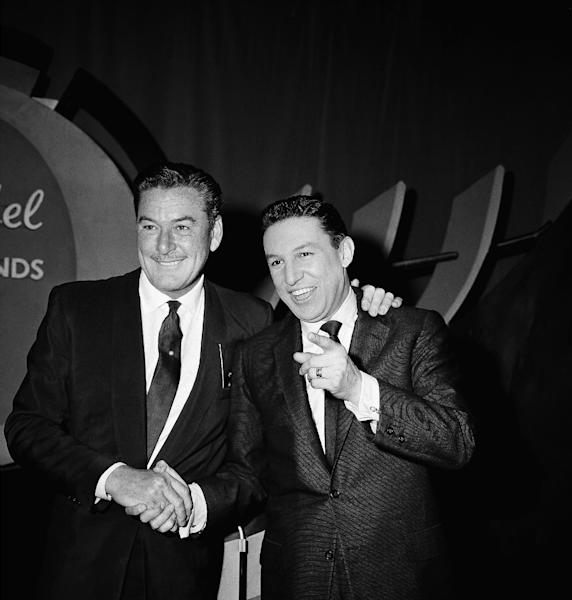 "FILE - In this Feb. 12, 1957 file photo, actor Errol Flynn, left, and television host Mike Wallace are shown before NBC's ""The Big Surprise"" TV quiz show, in New York. The quiz show is hosted by Mike Wallace. Wallace, the dogged, merciless reporter and interviewer who took on politicians, celebrities and other public figures in a 60-year career highlighted by the on-air confrontations that helped make ""60 Minutes"" the most successful primetime television news program ever, has died. He was 93. (AP Photo/Matty Zimmerman, File)"