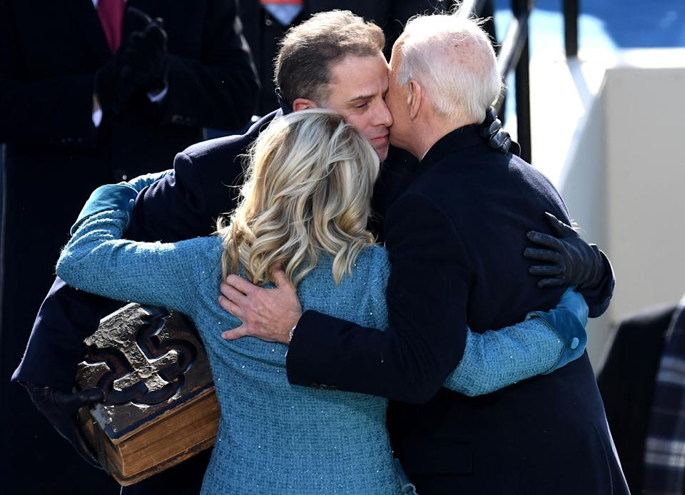 President Biden and first lady Jill Biden hug Hunter, who is holding a bible
