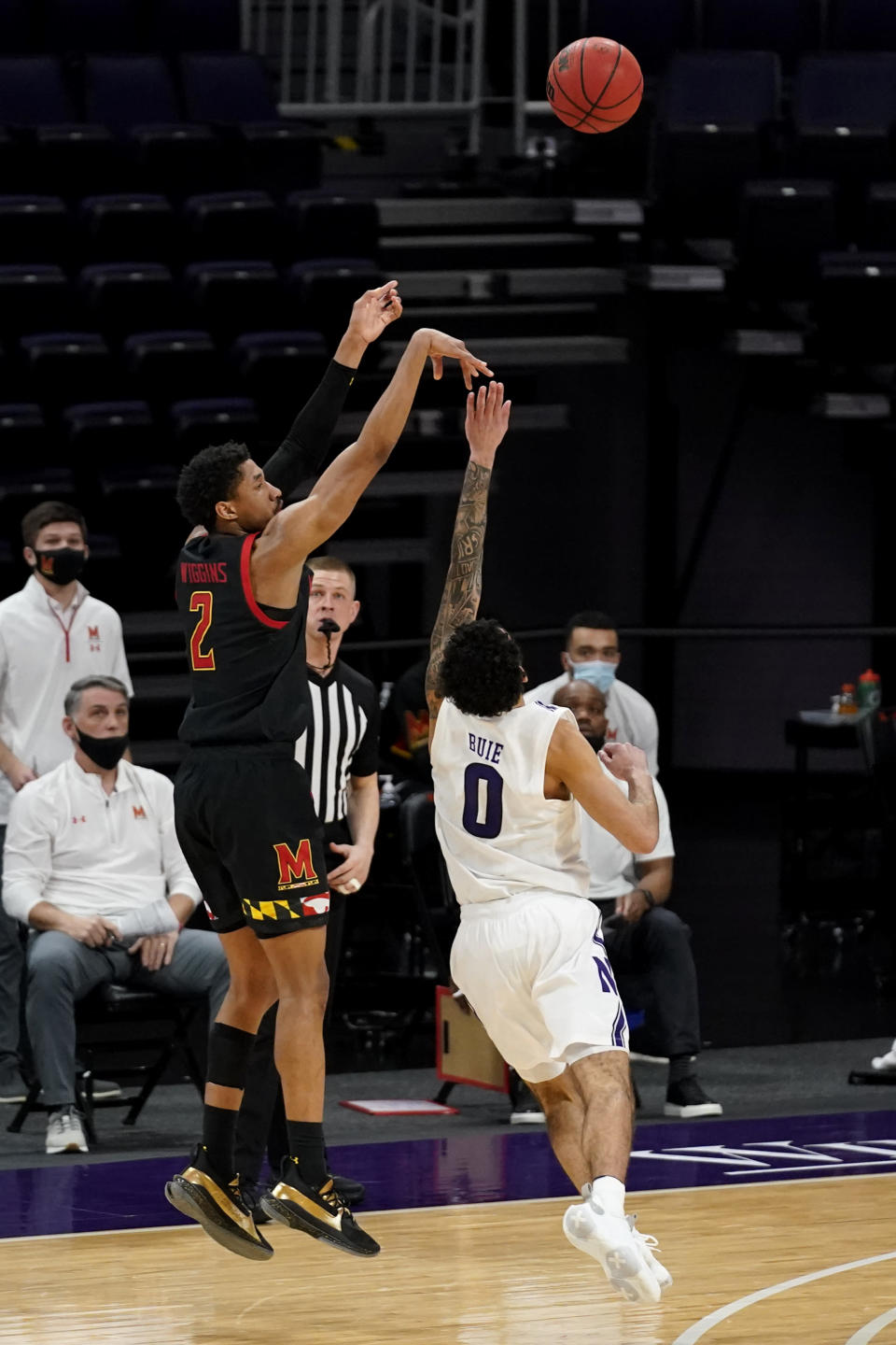 Maryland guard Aaron Wiggins, left, shoots over Northwestern guard Boo Buie during the second half of an NCAA college basketball game in Evanston, Ill., Wednesday, March 3, 2021. Northwestern won 60-55.(AP Photo/Nam Y. Huh)