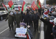 "An opposition supporter holds placard reading ""The best constitutional amendment is your resignation"" in front of column of Belarusian President Alexander Lukashenko's supporters in Minsk, Belarus, Monday, Oct. 19, 2020. The elderly rallied in Minsk once again on Monday to demand resignation of the country's President Alexander Lukashenko, as mass protests triggered by a disputed election continue to rock Belarus. Lukashenko's older supporters also gathered in the country's capital Monday for a pro-government rally. (AP Photo)"