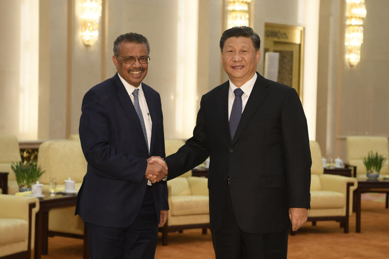 """FILE - In this Jan. 28, 2020, file photo, Tedros Adhanom Ghebreyesus, director general of the World Health Organization, left, shakes hands with Chinese President Xi Jinping before a meeting at the Great Hall of the People in Beijing. Throughout January, the World Health Organization publicly praised China for what it called a speedy response to the new coronavirus. It repeatedly thanked the Chinese government for sharing the genetic map of the virus """"immediately"""" and said its work and commitment to transparency were """"very impressive, and beyond words."""" But behind the scenes, there were significant delays by China and considerable frustration among WHO officials over the lack of outbreak data, The Associated Press has found. (Naohiko Hatta/Pool Photo via AP, File)"""