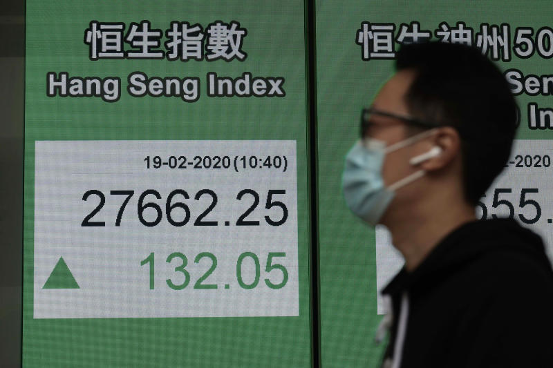 A man walks past an electronic board showing Hong Kong share index outside a local bank in Hong Kong, Wednesday, Feb. 19, 2020. Asian shares are mostly rising despite continuing fears about an outbreak of a new virus that began in China, which sent regional indexes mostly lower recently. (AP Photo/Kin Cheung)