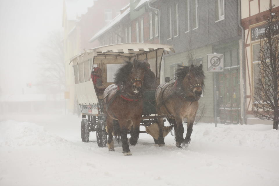 A horse-drawn carriage drives through the town in the snow flurry in Wernigerode, Germany, Sunday, Feb. 7, 2021. Low Tristan has caused huge amounts of snow in the Harz mountains, like here in Wernigerode. (Matthias Bein/dpa via AP)