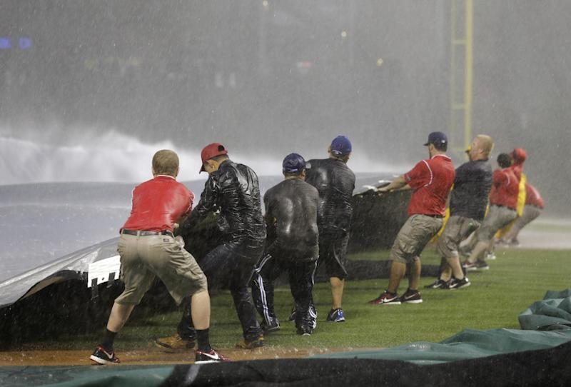 Texas Rangers grounds crew employees fight strong winds and rain as they attempt to lay out a tarp as a storm passed through the area before a baseball game against the Arizona Diamondbacks, Wednesday, May 29, 2013, in Arlington, Texas. (AP Photo/Tony Gutierrez)