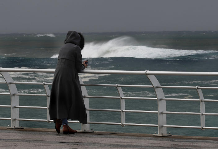 A woman watches waves on the Mediterranean Sea promenade, in Beirut, Lebanon, Wednesday, Feb. 17, 2021. Breaking a warm spell, Storm Joyce that hit Lebanon brought heavy rainfall, a sharp drop in temperatures and the heaviest snow fall in Lebanon this year. (AP Photo/Hussein Malla)