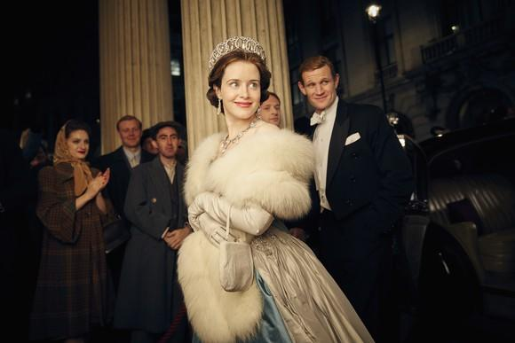"A scene from Netflix original ""The Crown"" with Claire Foy and Matt Smith, showing a striking young woman smiling, wearing a stole and a crown, with a man in a tuxedo in the background."