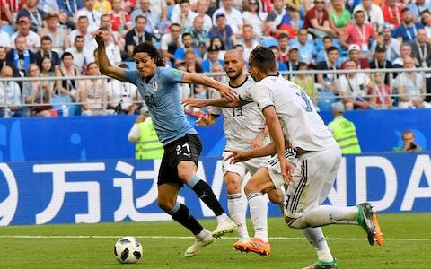 Uruguay's Edinson Cavani, left, take the ball away from Russia's Ilya Kutepov, right, and Fyodor Kudryashov during the group A match between Uruguay and Russia at the 2018 soccer World Cup at the Samara Arena in Samara, Russia, Monday, June 25, 2018 - Credit: AP