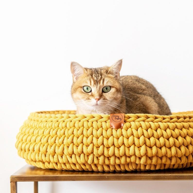 """<p>This rounded nest of a bed is perfect your cat to curl up and snuggle in. Made in Holland, the raised sides help with comfort and a sense of security, and the recycled oeko-tex cotton provides just the right sturdiness. Each one comes in a decidedly modern hue—mustard yellow, blush pink, or terracotta.</p> <p><strong><em>Shop Now: </em></strong><em>Sunny Baskets Chunky Crocheted Cat Basket, starting from $73.89, <a href=""""https://www.awin1.com/cread.php?awinmid=6220&awinaffid=272513&clickref=MSL10ModernCatBedsforaWellDesignedHomeaharperCatGal7985721202010I&p=https%3A%2F%2Fwww.etsy.com%2Flisting%2F678245464%2Fhandmade-cat-basket-recycled-cotton"""" rel=""""nofollow noopener"""" target=""""_blank"""" data-ylk=""""slk:etsy.com"""" class=""""link rapid-noclick-resp"""">etsy.com</a></em><em>.</em></p>"""