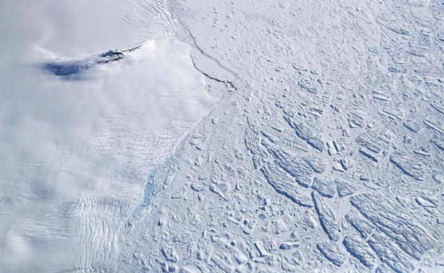 <p>Icebergs and sea ice (right) float next to land ice (left), as seen from NASA's Operation IceBridge research aircraft, near the coast of the Antarctic Peninsula region, on Nov. 3, 2017, above Antarctica. (Photo: Mario Tama/Getty Images) </p>