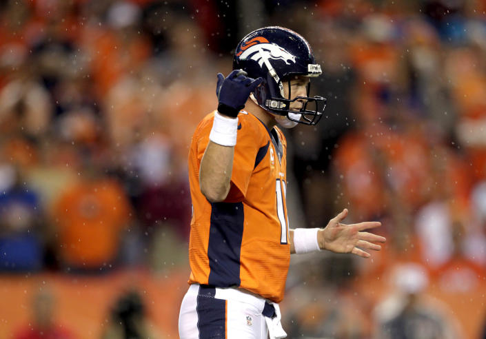Denver Broncos quarterback Peyton Manning makes a call in the rain during the first half of an NFL football game against the Baltimore Ravens, Thursday, Sept. 5, 2013, in Denver. (AP Photo/Joe Mahoney)