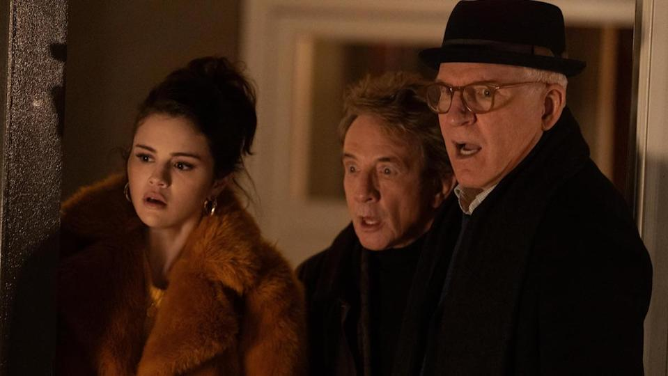 A young woman in a big coat, an older man, and a second taller older man in glasses and a hat all looked shock as they stand in a doorway of an apartment