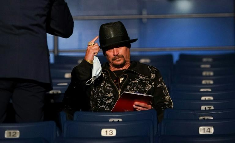 Kid Rock, one of the few music stars to vocally back President Donald Trump, takes off his mask as he sits down to attend the final presidential debate at Belmont University in Nashville, Tennessee