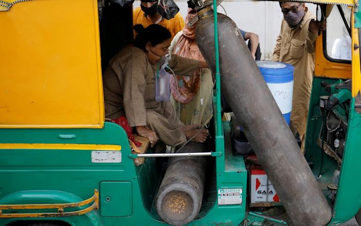 Aminbanu Memon wearing an oxygen mask sits in an autorickshaw waiting to enter a COVID-19 hospital for treatment