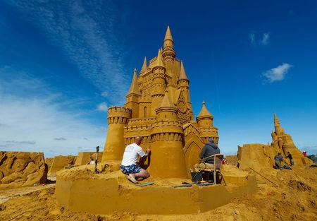 """A sand carver works on a sculpture during the Sand Sculpture Festival """"Disney Sand Magic"""" in Ostend"""