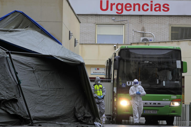 A member of the Emergency Army Unit wearing a protective suit to protect from the coronavirus stands next to a bus as Spain announced what is believed to be the highest rise in Covid-19 deaths in the world so far. (AP Photo/Manu Fernandez)