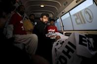 Abdul Majeed, brother of Shafqat Hussain who was convicted of killing a child in 2004, sits in an ambulance beside the body of Safqat after his execution in Karachi, Pakistan, August 4, 2015. REUTERS/Akhtar Soomro