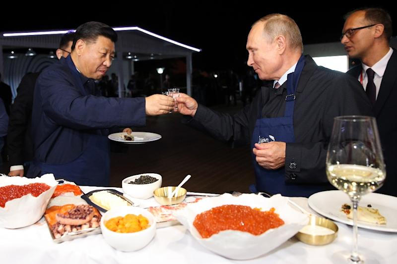 "Russian President Vladimir Putin toasts with his Chinese counterpart Xi Jinping as they tasted pancakes they cooked while visiting ""The Far East Street"" exhibition (AFP Photo/Sergei BOBYLYOV)"