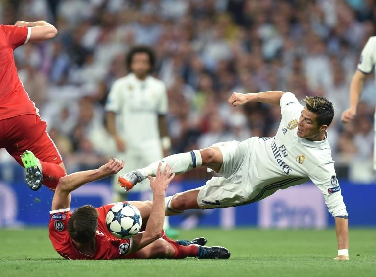 Bayern Munich's Spanish midfielder Xabi Alonso and Real Madrid's Portuguese striker Cristiano Ronaldo (right) vie for the ball during their UEFA Champions League quarterfinal match in Madrid, Spain, on April 18, 2017