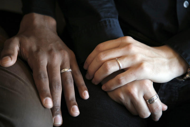 "In this photo taken on Monday, Oct. 22, 2012, the hands of Ludovic-Mohamed Zahed, right, who married his live-in partner Qiyaammudeen Jantjies, left, in South Africa, where gay marriage is recognized, during an interview with the Associated Press in Sevran, outside Paris. A plan to legalize same-sex marriage and allow gay couples to adopt was a liberal cornerstone of French President Francois Hollande's election manifesto earlier this year. It looked like a shoo-in, supported by a majority of the French, and an easy way to break with his conservative predecessor. But that was then, Now, as the Socialist government prepares to unveil its draft ""marriage for everyone"" law Wednesday, polls show wavering support for the idea and for the president amid increasingly vocal opposition in this traditionally Catholic country. Ludovic-Mohamed Zahed, who married his live-in partner Qiyaammudeen Jantjies in South Africa, where gay marriage is recognized, is already seeking instruction from his local town council to get his marriage recognized in France as soon as he can. (AP Photo/Christophe Ena)"