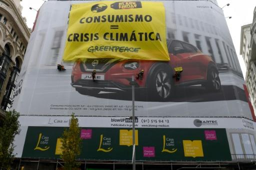 """Greenpeace activists on Friday unfurled a banner on the Gran Via, a main shopping artery in the Spanish capital, which read """"Consumerism = Climate Crisis."""""""