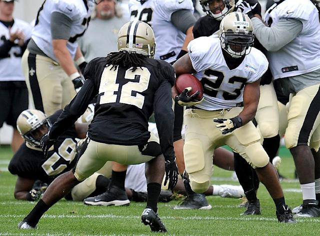 New Orleans Saints running back Pierre Thomas (23) tries to get around New Orleans Saints defensive back Pierre Warren (42) during the teams NFL football training camp in White Sulphur Springs, W.Va., Friday, Aug. 1, 2014. (AP Photo/Chris Tilley)