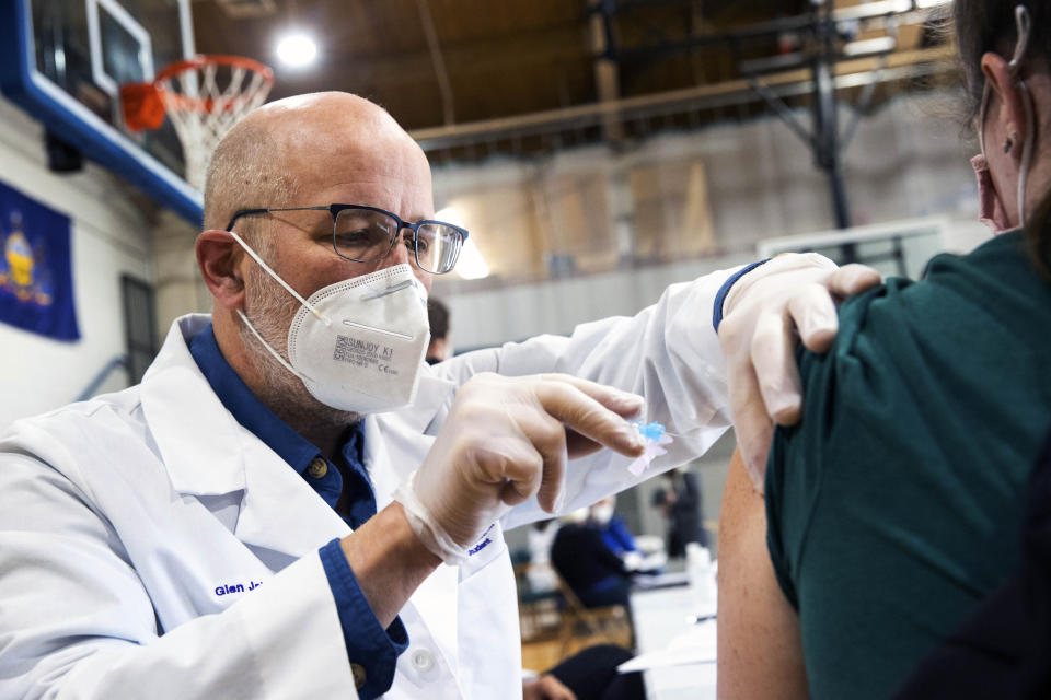 University of Scranton nursing student Glen Johnson administers the Moderna COVID-19 vaccine to a medical professional during a clinic at the Throop Civic Center in Throop, Pa. on Saturday, Jan. 9, 2021. The Lackawanna County Medical Society had about 400 doses of the Moderna vaccine on hand to administer to people in Pennsylvania's Phase 1A group of the vaccine rollout plan, which is limited to healthcare personnel and long-term care facility residents. (Christopher Dolan/The Times-Tribune via AP)