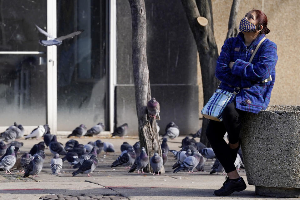 FILE - In this Nov. 12, 2020, a woman wears a mask and looks up as she waits for a bus at a bus stop in Chicago. From New Mexico to New Jersey to Chicago, states and cities were ordering or imploring residents to stay home to help stem a rising tide of coronavirus infections that has prompted fears the nation's health care system will quickly be overwhelmed. (AP Photo/Nam Y. Huh, File)