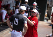 North Carolina State pitching coach Clint Chrysler, right, speaks with right handed pitcher Dalton Feeney (19) in the dugout during a delay due to health and safety protocols before their baseball game against Vanderbilt in the College World Series Friday, June 25, 2021, at TD Ameritrade Park in Omaha, Neb. (AP Photo/Rebecca S. Gratz)