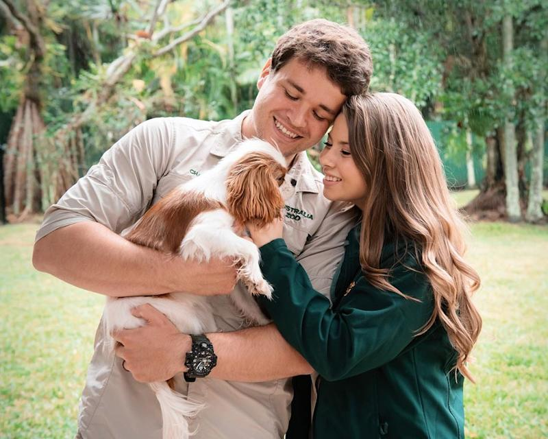 Bindi Irwin and her husband, Chandler Powell holding their dog, Piggy