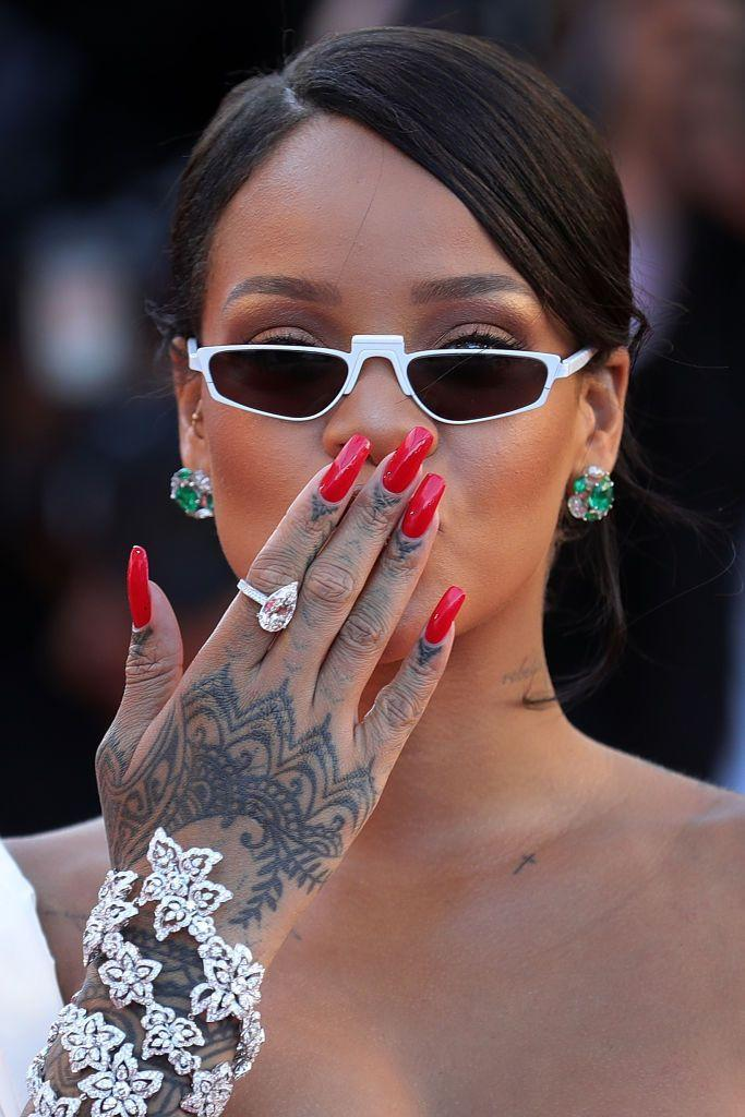 """<p>Rihanna's hands are some of the most decorated parts of her body. Her right hand in particular has detailed henna-inspired inking running up from the wrist to the bottom of her fingers, which unsurprisingly were the works of Bang Bang.</p><p><a href=""""https://www.eonline.com/uk/news/475546/rihanna-gets-new-henna-inspired-tattoo-all-over-her-hand-see-the-exclusive-pics"""" rel=""""nofollow noopener"""" target=""""_blank"""" data-ylk=""""slk:The artist told E!"""" class=""""link rapid-noclick-resp"""">The artist told E!</a> in 2013 that he spent five hours on the design, explaining: 'The inspiration was henna art, we wanted something really decorative, feminine and sexy. We thought that was the closest in style where we could shift and make it look decorative.'</p>"""