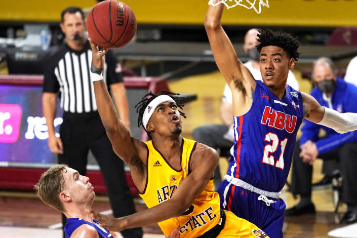 Arizona State guard Caleb Christopher, center, shoots between Houston Baptist guard Ty Dalton, left, and Pedro Castro (21) during the first half of an NCAA college basketball game, Sunday, Nov. 29, 2020, in Tempe, Ariz. (AP Photo/Rick Scuteri)