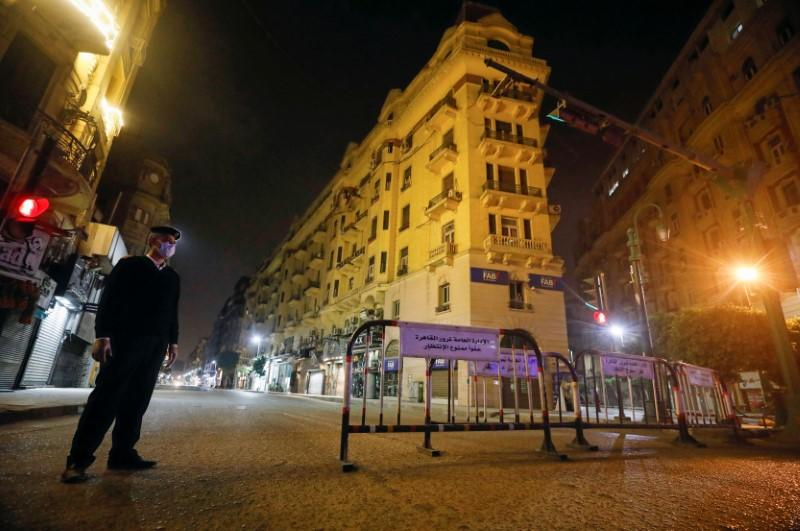 A police officer stands at the Qasr El Nil street during the first day of a two-weeks night-time curfew which ordered by the Egyptian Prime Minister Mostafa Madbouly to contain the spread of the coronavirus disease (COVID-19), in Cairo