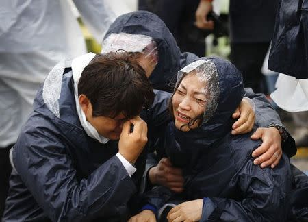 Family members of passengers missing on the overturned South Korean ferry Sewol, react at the port in Jindo