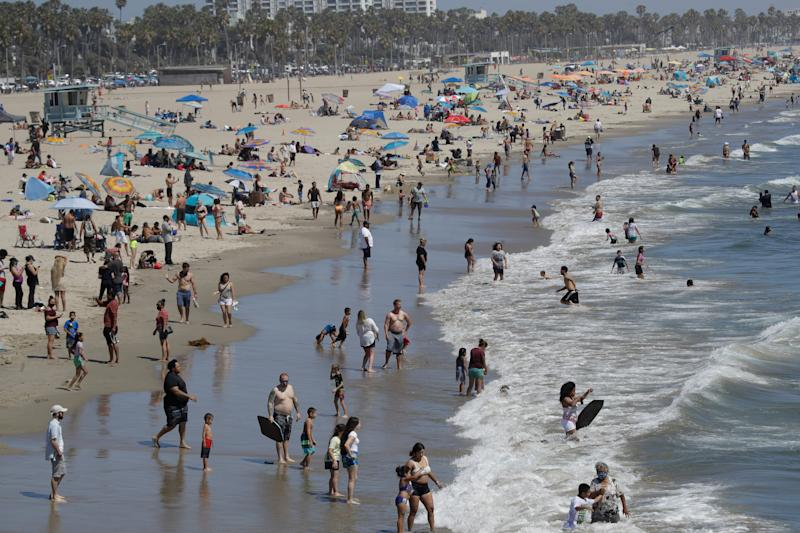 A heat wave has brought crowds to California's beaches as the state grappled with a spike in coronavirus infections and hospitalizations.