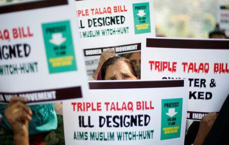 "FILE PHOTO: Muslim women hold placards during a protest against a bill passed by India's lower house of Parliament last week that aims at prosecuting Muslim men who divorce their wives through the ""triple talaq,"" or instant divorce, in New Delhi, India January 4, 2018. REUTERS/Adnan Abidi/File Photo"