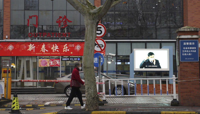 An elderly woman with a face mask walks past the entrance to the outpatient ward with a video display showing prevention methods in Shanghai on Monday, Jan. 27, 2020. The government of Shanghai, a metropolis of 25 million people and a global business center, extended the holiday by an additional week within the city to Feb. 9. It ordered sports stadiums and religious events closed. (AP Photo/Erika Kinetz)