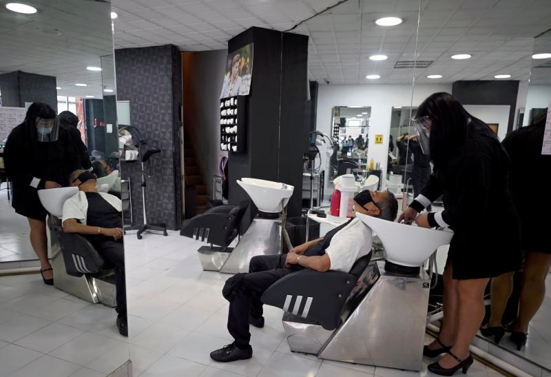 An employee at a beauty salon attends a client, during the COVID-19 pandemic, in Mexico City on June 29, 2020. - Starting this week Mexico City is allowing the reopening of shops, street markets and athletic complexes but with limited capacity and hours. Hotels and restaurants in the capital will reopen at about 30% seating capacity. (Photo by ALFREDO ESTRELLA / AFP) (Photo by ALFREDO ESTRELLA/AFP via Getty Images)