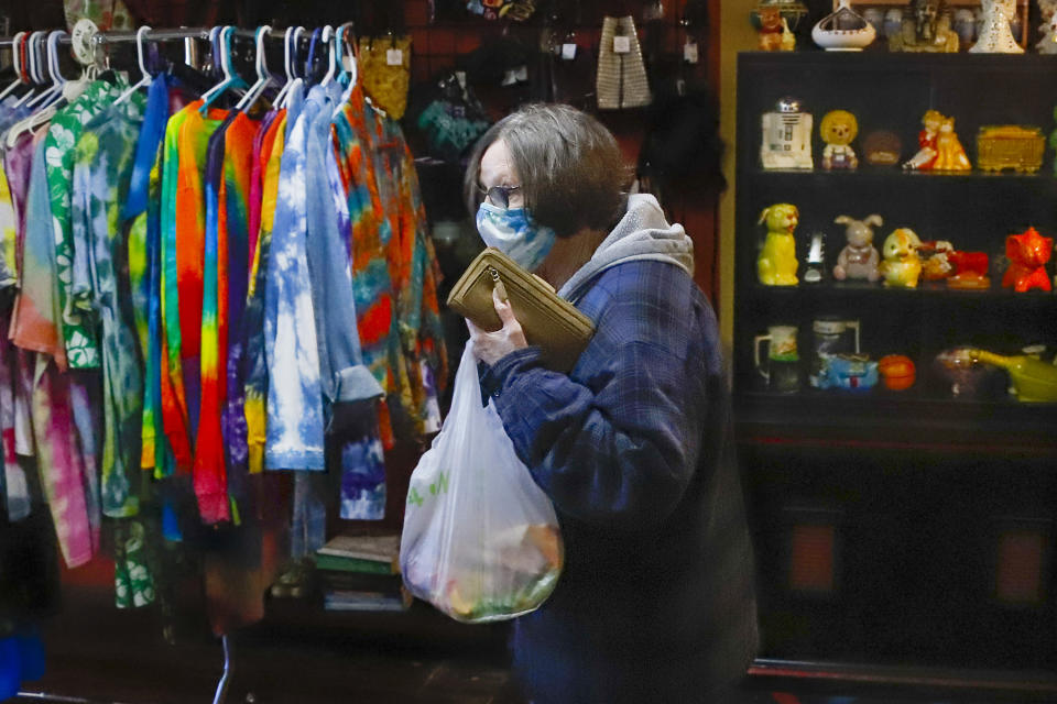A patron at the Harmony Emporium makes her way past the tie-dye shorts after making a purchase on Saturday, Nov. 28, 2020, in Harmony, Pa. Many smaller businesses hope to see a boost on the Saturday following Thanksgiving, traditionally known as Small Business Saturday. (AP Photo/Keith Srakocic)