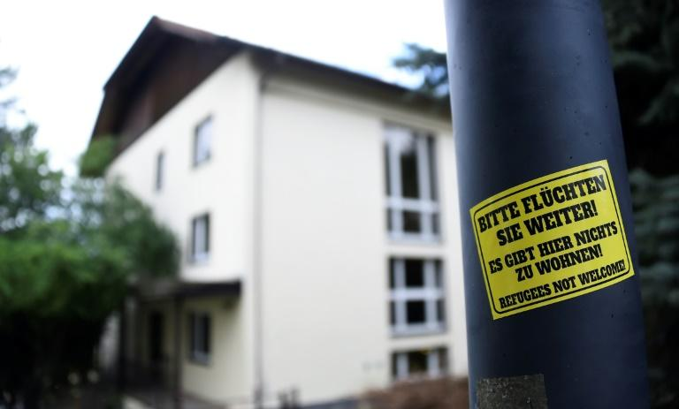 A sticker reading 'Please keep on fleeing - here is no place for you - refugees not welcome' is pinned at a lantern next to a refugee centre in Freital, eastern Germany