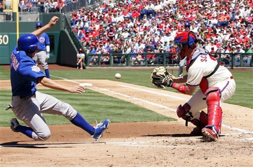 Chicago Cubs' Tony Campana slides into home as Philadelphia Phillies catcher Brian Schneider waits for the throw during the third inning of a baseball game Sunday, April 29, 2012, in Philadelphia. Campana was safe. (AP Photo/Tom Mihalek)
