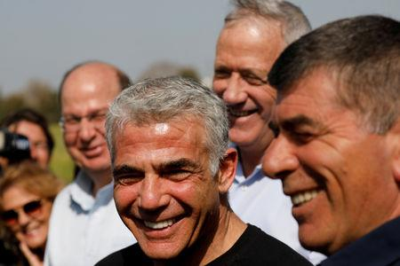 FILE PHOTO: Benny Gantz, head of Blue and White party, stands next to fellow party candidates during a visit to a kibbutz in Israel outside the northern Gaza Strip, March 13, 2019. REUTERS/Amir Cohen/File Photo