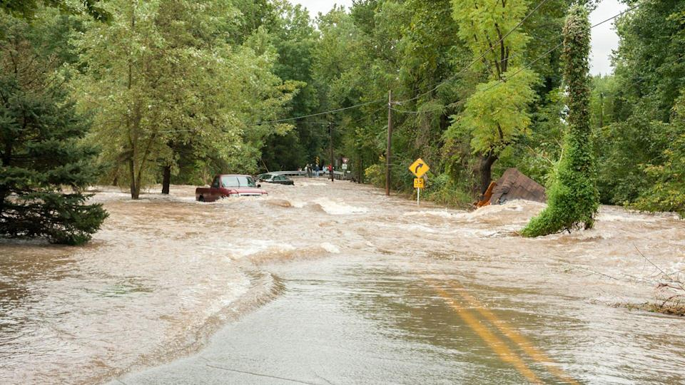 flooded road with cars trying to drive through