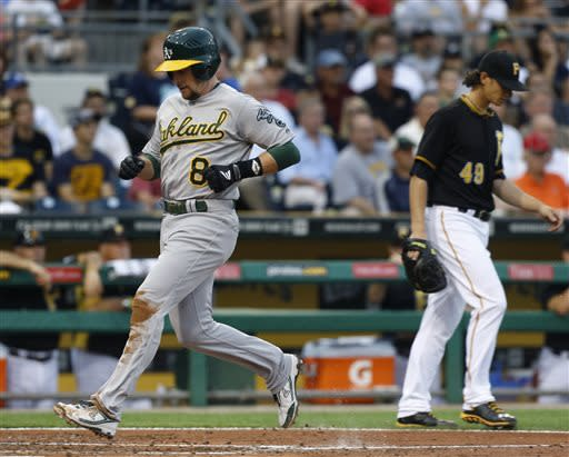 Oakland Athletics' Jed Lowrie (8) scores from third on a sacrifice fly by Josh Donaldson past Pittsburgh Pirates starting pitcher Jeff Locke (49) in the fourth inning of the baseball game on Monday, July 8, 2013, in Pittsburgh. (AP Photo/Keith Srakocic)