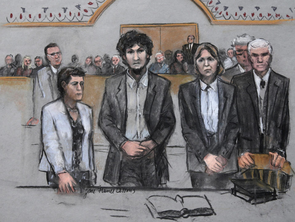 FILE— In this May 15, 2015 file courtroom sketch by Jane Flavell Collins, Boston Marathon bomber Dzhokhar Tsarnaev, center, stands with his defense attorneys as a death by lethal injection sentence is read at the Moakley Federal court house in the penalty phase of his trial in Boston. Collins, a courtroom sketch artist who drew pictures of defendants in some of the most notorious cases tried in federal court in Boston, died Sunday, May 16 2021, according to her family. She was 84. (Jane Flavell Collins via AP)