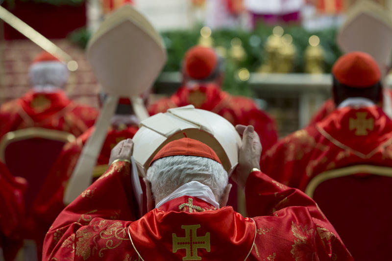 A cardinal puts on his mitre hat during a Mass for the election of a new pope, inside St. Peter's Basilica , at the Vatican, Tuesday, March 12, 2013. Cardinals enter the Sistine Chapel on Tuesday to elect the next pope amid more upheaval and uncertainty than the Catholic Church has seen in decades: There's no front-runner, no indication how long voting will last and no sense that a single man has what it takes to fix the many problems. (AP Photo/Andrew Medichini)